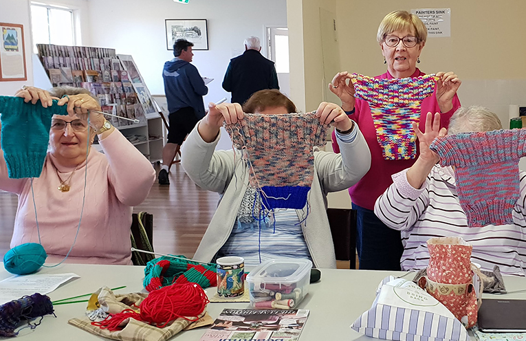 Hanna Reher, Wendy Harvey, Gael Horvat, Lyn Cummings. Standing - Sheila Francis, Regina Baker of the Port Stephens Community Arts Centre with some of the Jumpers that they have knitted to help farmers save their lambs.