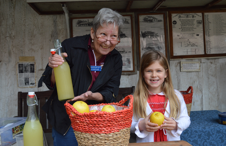 Pia Ryeland shows Elizabeth Kilday (5) how to make lemonade the old fashioned way.