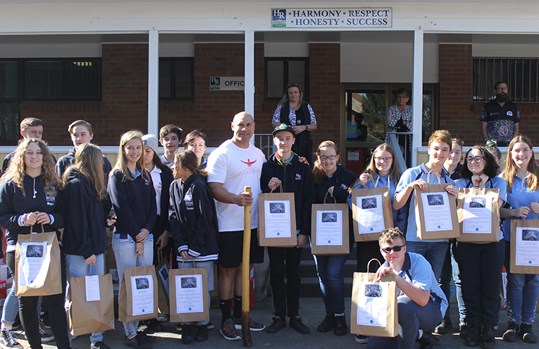 Students from Hunter River High School with Sione Finefeuiaki and their collection of student packs.
