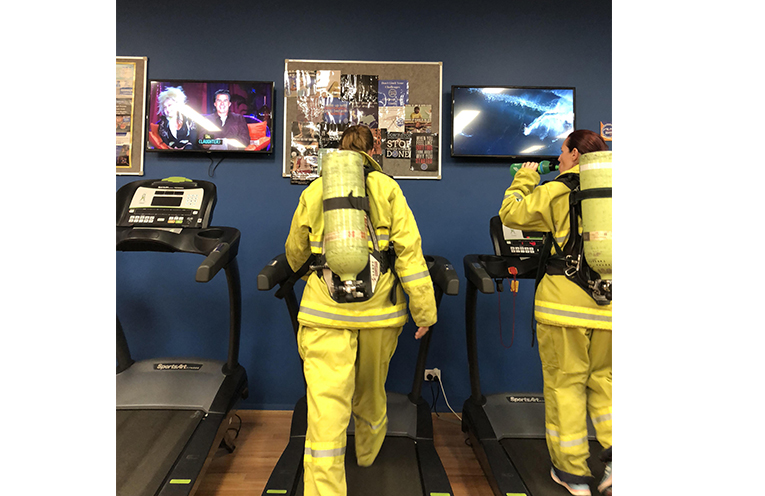 Firefighters in full kit, training at the gym to get used to climbing with over 20kg of equipment.