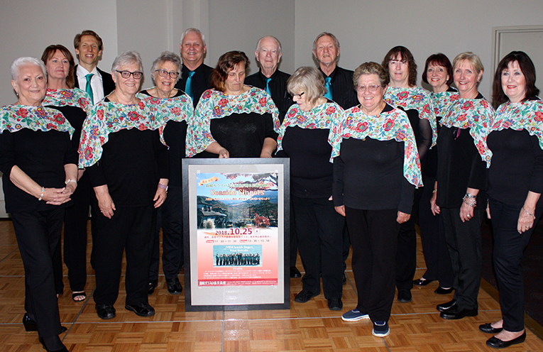 Seaside Singers tour group with poster for their Hakone Venetian Glass Museum performance Hazel Basnett, Helen Jackson, Ellery Durrant (music director), Jeanette Antrum, Helen Revell, Wayne Livermore, Ria Quayle, Peter Cowling, Cathy McWilliam, Colin Murdoch, Carole Delaney, Nerida O'Shea, Ellen Robson, Sabine Dow and Delohrey Olsson.