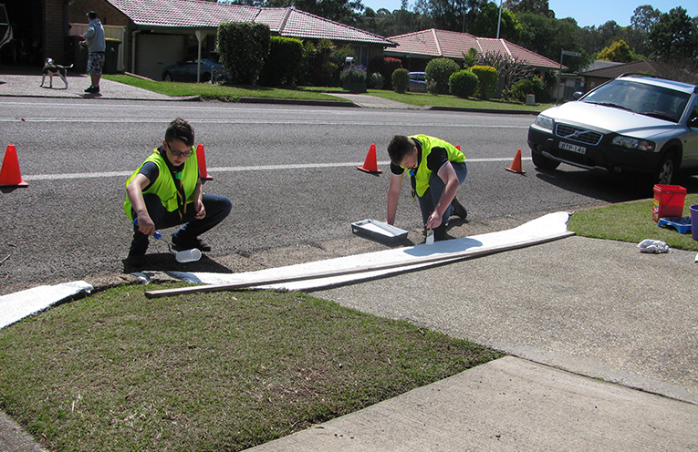 Raymond Terrace Scouts painting kerb wings and drive on strip for a resident in Chifley Drive, Raymond Terrace.