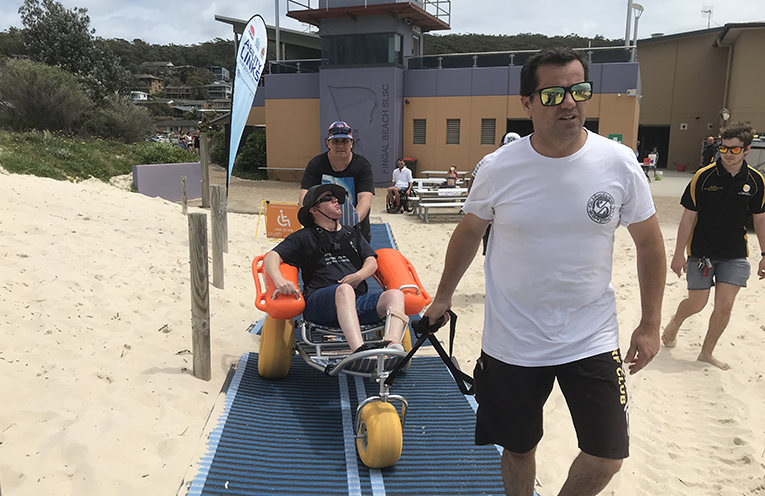 Andy Fielding in the Mobichair with Craig Dunning and Fingal Surf Lifesaving Clubs Marty Thompson. Photo by Marian Sampson.
