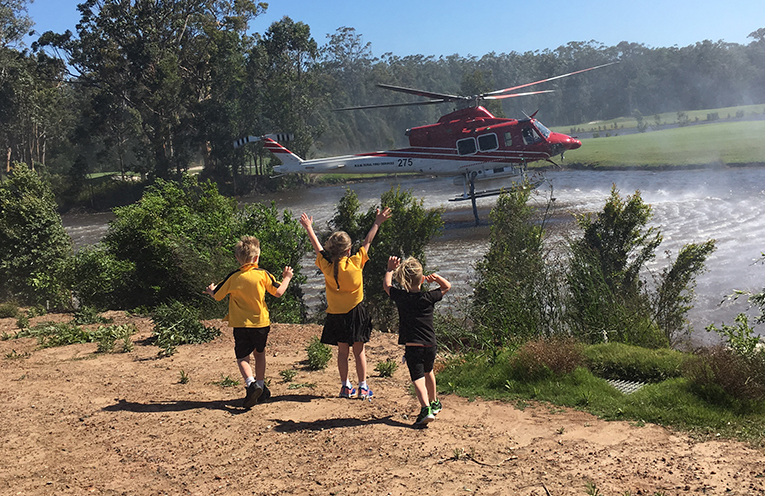 The Petterson Children, waving their thanks in excitement to the helicopters collecting more water for the Campvale fire. Photo by Christelle Petterson.