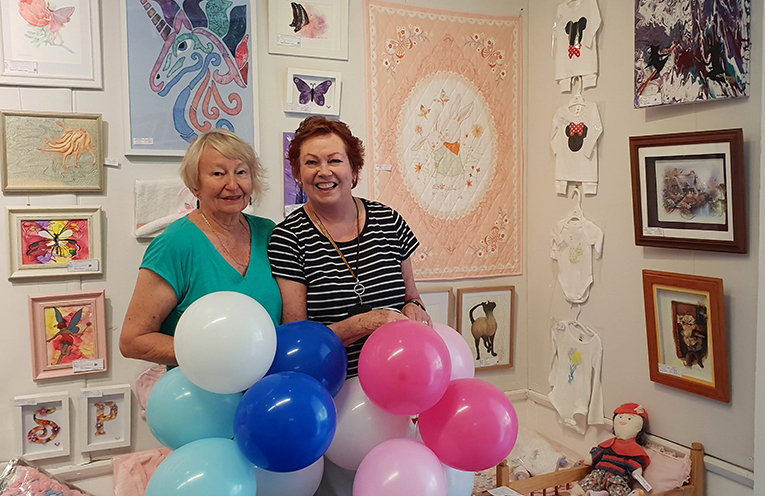 Nada O'Loughlin-Yonge and Judy Warren taking great delight in hanging the Children's World Exhibition.