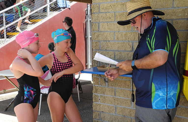 Coach Michael Abel debriefing Caitlin and Georgia McDonald after their race.
