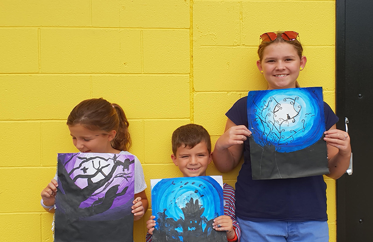 Tilligerry children  Zoey, Noah, and Grace proudly showing their acrylic spooky sky creations.