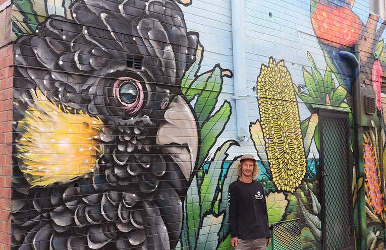 Rhys Fabris with the partially completed mural at Nelson Bay. Photo by Marian Sampson.
