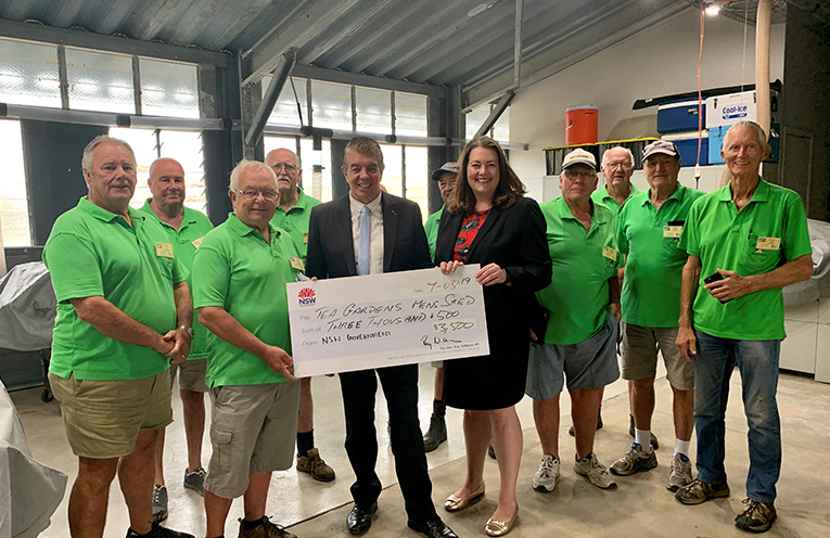 TEA GARDENS MEN'S SHED: Minister Ray Williams and Liberal's Jaimie Abbott present cheque for defibrillator.