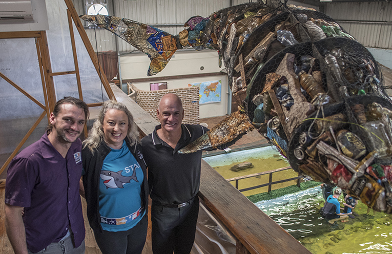 "Ryan Pereira with visual artist Matt Johnstone and Lia Pereira showcasing ""Agutfull"" the shark - representing just three percent of the waste collected at the first Marsh Road Clean-Up by Sea Shelter."