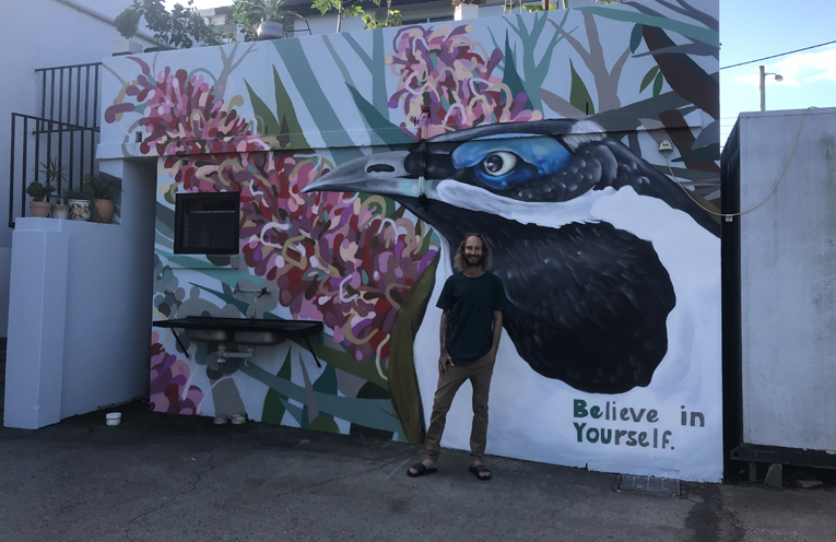 Rhys Fabris with his latest larger than life mural. Photo by Marian Sampson.