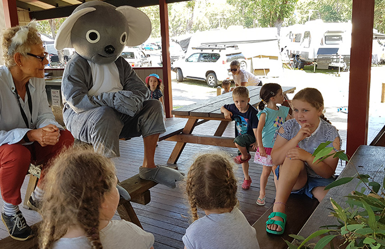 Adrienne Ingram and koala Peter Rogers talking to children at the Reflections Holiday Camp, Hawks Nest.