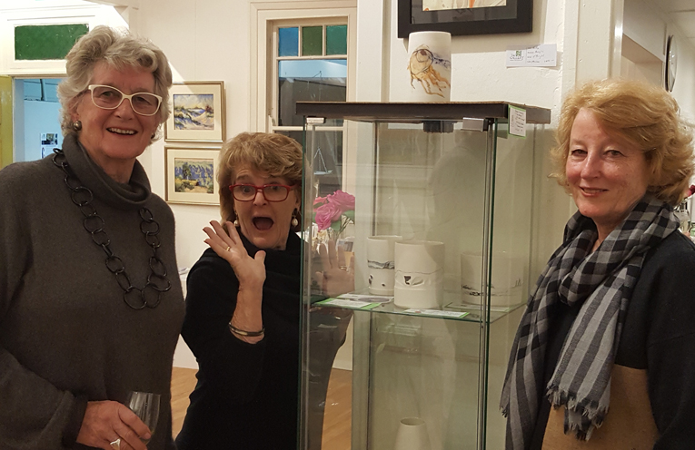 Left to right: Winner of the Ceramics category, Rosie Lucas, with Lee Anderson and judge Anne Latter. Rosie's ceramics are in the glass-front cabinet between the ladies.